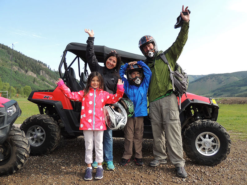 Family with hands in the air in front an ATV