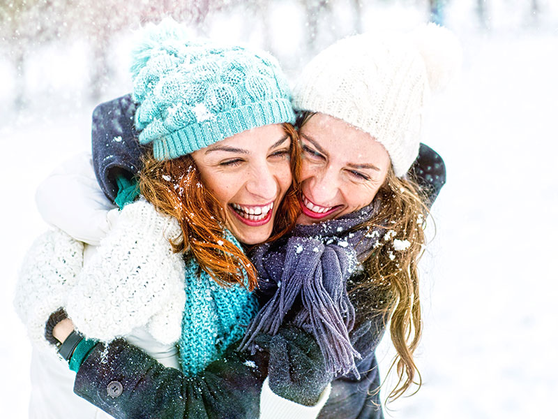 Friends hugging in the snow